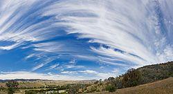 Een hemel van cirruswolken (links) die overgaat in cirrostratus (midden-rechts) met wat cirrocumulus (rechtsboven).
