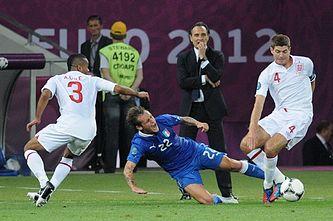 Alessandro Diamanti (blauw 22) pakt Steven Gerrard (wit 4) aan op Euro 2012.