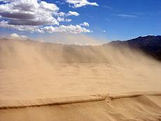 De wind blaast zand van deze duin in de Mojave woestijn, Californië