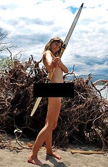 Een vrouw die naakt boogschieten beoefent