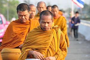 Thaise boeddhistische monniken lopen 's morgens vroeg om aalmoezen te verzamelen.
