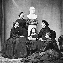 亡き父アルバート王子(1862年)の胸像の下で喪服を着て撮影されたヴィクトリアの5人の娘(アリス、ヘレナ、ベアトリス、ヴィクトリア、ルイーズ)。