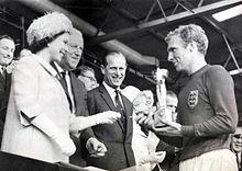 De koningin overhandigt de wereldbeker van 1966 aan Bobby Moore, aanvoerder van het zegevierende Engelse team. De wedstrijd werd gespeeld tussen Engeland en West-Duitsland op 30 juli 1966 in het Wembley Stadium. Engeland won met 4-2 na extra tijd.
