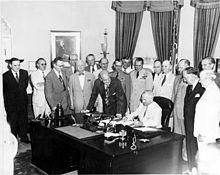 Il presidente Truman firma l'emendamento del National Security Act del 1949 con ospiti nello Studio Ovale.