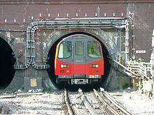 """Pseudonim """"the Tube"""" pochodzi od okrągłych tuneli, którymi jeżdżą niektóre pociągi. Pokazany """"pociąg rurowy"""" znajduje się w tunelu w pobliżu stacji Hendon Central, Londyn."""